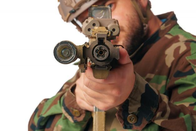 Airsoftspeler die met zijn geweer streven dat op wit wordt geïsoleerd