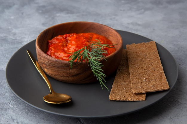 Ajvar, lutenitsa, pinjur, harissa met brood op een bord