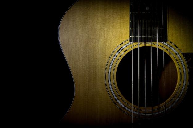 Akoestische gitaar die op zwarte achtergrond, rustig beeld wordt geïsoleerd