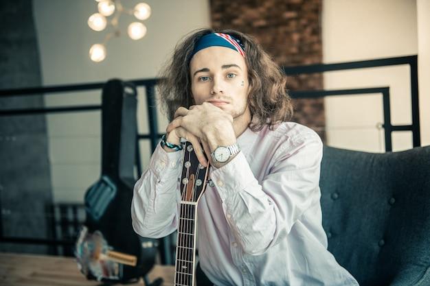 Akoestische gitaar dragen. vermoeide knappe man met tatoeage op het gezicht die beide handen op de hals van zijn gitaar legt