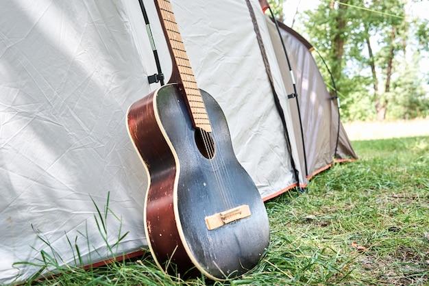 Akoestische gitaar in de buurt van een campingtent in een bos