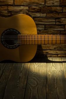 Akoestische gitaar ligt op de achtergrond van een bakstenen muur.