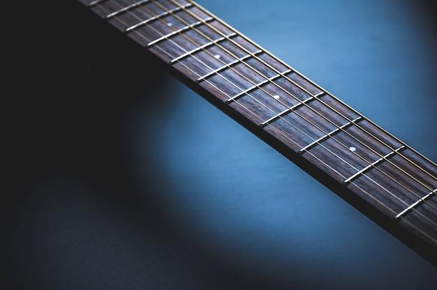 Akoestische gitaar, muziekinstrument dat tegen een donkere blackvmuur rust met exemplaarruimte, close-up van houten klassieke gitaar