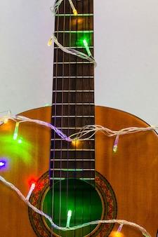 Akoestische gitaar omwikkeld met kleurrijke guirlande. kerst- en nieuwjaarsmuziekcadeau als achtergrond