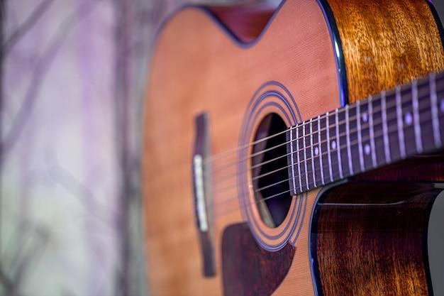 Akoestische gitaar op een mooi gekleurde muur. het concept van snaarinstrumenten.