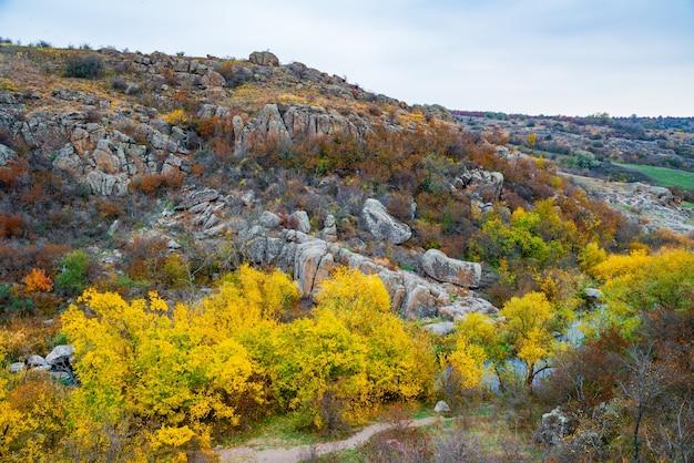 Aktovsky canyon en herfstbomen en grote stenen rotsblokken rondom