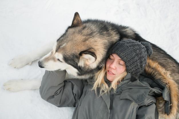 Alaskan malamute liegen en knuffelen met vrouw in winter woud. detailopname.
