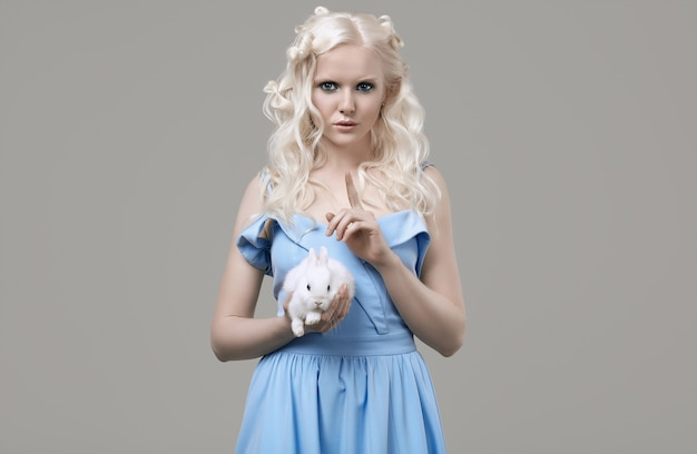 Albino blond meisje in elegante jurk poseren met schattige kleine konijn