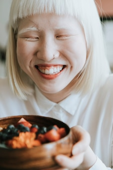 Albino-meisje met een gezond ontbijt in een café