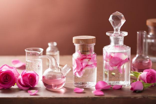 Alchemie en aromatherapie bezet met roze bloemen en flacons