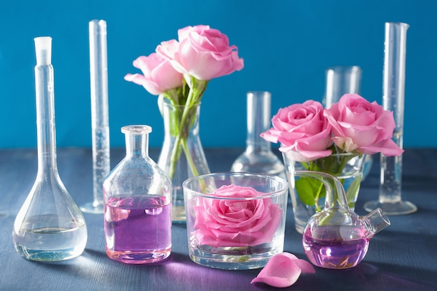 Alchemie en aromatherapie set met roze bloemen en chemische kolven
