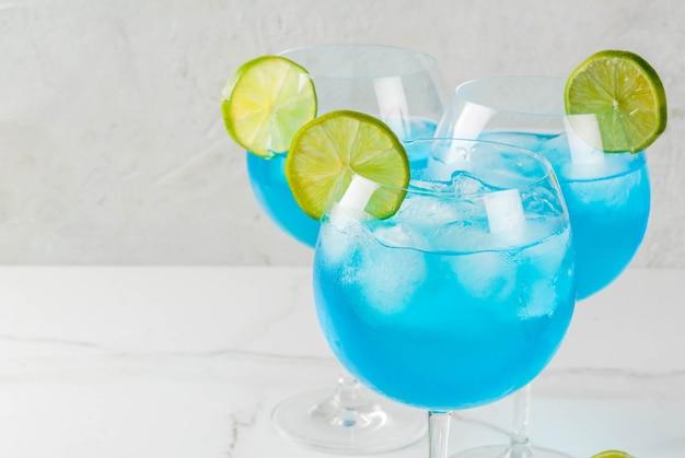 Alcohol drinken. glazen met een blauwe alcoholische cocktail met ijs en limoen garnituur. blue curacao. likeur.