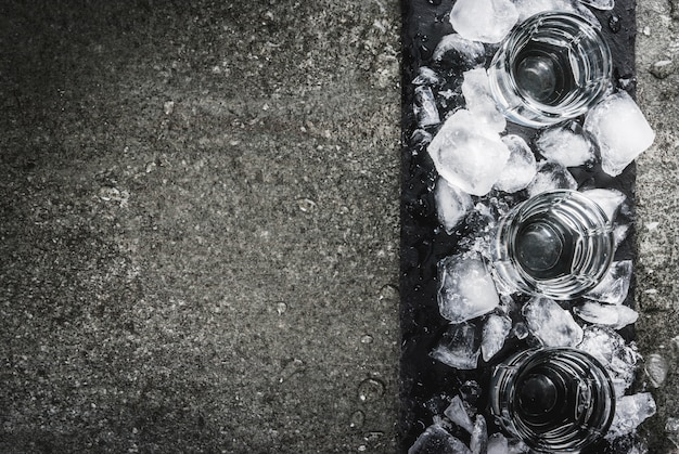 Alcohol en cocktails. drie glazen wodka op een leien dienblad, met ijs. op een zwarte stenen tafel, bovenaanzicht