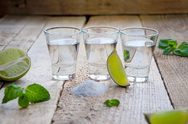 Alcohol shot drinken. zilveren tequila met limoen, zout en groen op de houten tafel