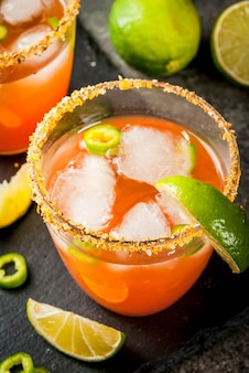 Alcohol. traditionele mexicaanse zuid-amerikaanse cocktail. pittige michelada met hete jalapeno-pepers en limoen. op een donkere stenen tafel. copyspace