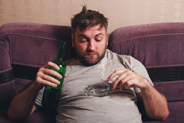 Alcohol verslaafde man rookt sigaret