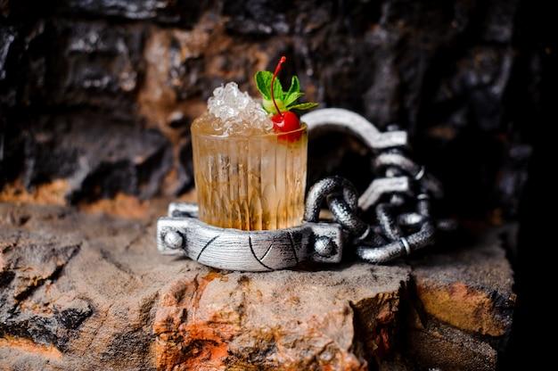Alcoholcocktail met gemalen ijs, rode kers en munt.