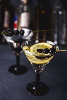 Alcoholcocktail met splash. droge martini met zwarte olijven. mondcocktail in martini-glas over donkere achtergrond. martini-glazen zijn op de bar.