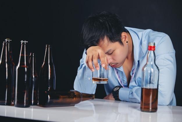 Alcoholische aziatische man die whisky met veel flessen drinkt