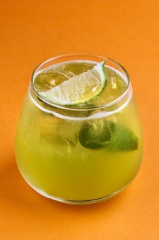 Alcoholische cocktail basilicum smash met groene basilicum, op een oranje achtergrond