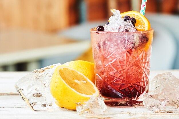 Alcoholische cocktail bestaande uit krenten, bramen en likeur in een glas en citroen op een houten tafel