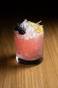 Alcoholische cocktail bramble op basis van gin, bramenlikeur, citroensap en suikersiroop, versierd met bramen en citroenschil in een transparant glas op een houten tafel
