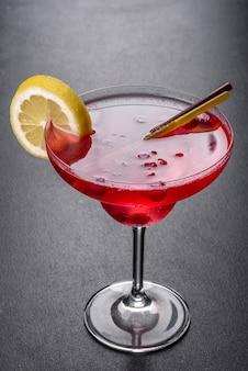 Alcoholische cocktail is kosmopolitisch met ijs, bessen en cocktailbuizen op een zwarte tafel
