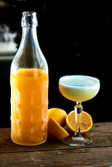 Alcoholische cocktail limoncello sauer diende in een glas wijnglas en fles op houten tafel op zwarte achtergrond