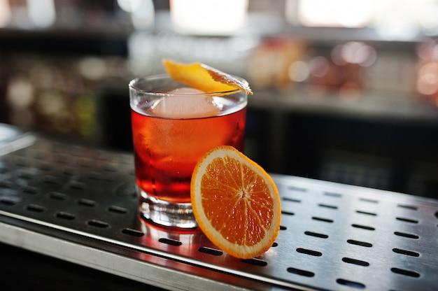 Alcoholische cocktail met ijs en sinaasappel in glas op barlijst