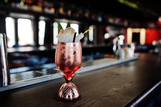 Alcoholische cocktail met ijs in bronsglas op barlijst