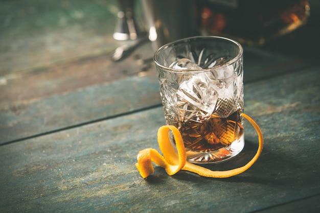 Alcoholische cocktail met sinaasappelschil en ijs