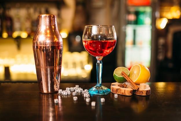 Alcoholische cocktail, shaker en dobbelstenen op toog