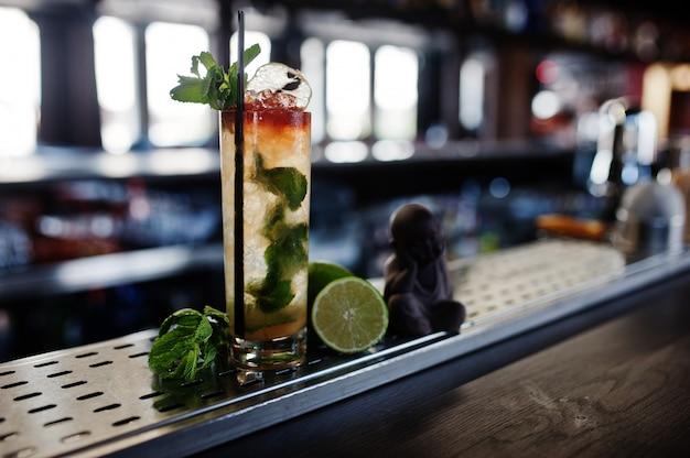 Alcoholische lange cocktail met munt en limoen in glas bij barlijst