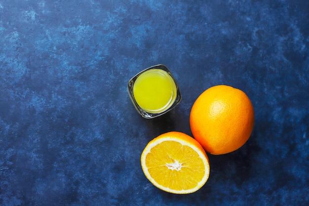 Alcoholische oranje drank in geschoten glas met oranje plak en sinaasappel op donkere achtergrond