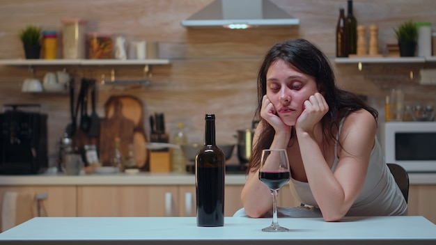 Alcoholische persoon met hoofdpijn die zich probeert te onthouden. ongelukkige vrouw die aan migraine, depressie, ziekte en angst lijdt, zich uitgeput voelt met symptomen van duizeligheid met alcoholismeproblemen.