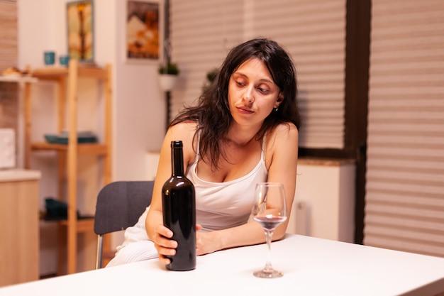 Alcoholische vrouw met een fles wijn die depressief is. ongelukkige persoon ziekte en angst gevoel uitgeput met alcoholisme problemen.