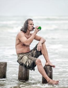 Alcoholisme. man van middelbare leeftijd met een naakte torso zit op houten palen op het strand en drinkt alcohol