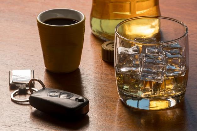 Alcoholmisbruik met glas whisky met ijs en autosleutel op tafel.