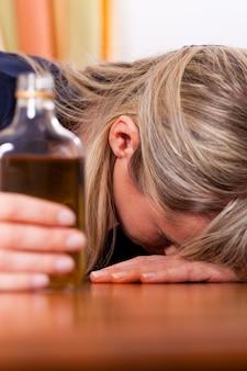 Alcoholmisbruik - vrouw die te veel cognac drinkt