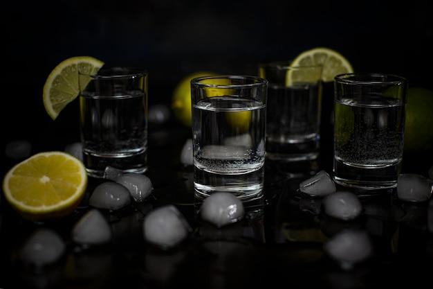 Alcoholschoten met limoen en ijsblokjes op zwart