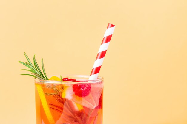 Alcoholvrije cocktail met citroen en framboos en rozemarijn op een beige achtergrond. bovenkant van glas met limonade en gestreept wegwerprietje voor zomerse hitte.