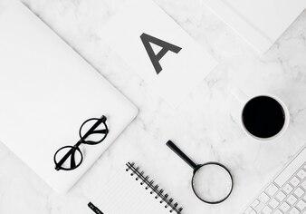 Alfabet a op papier; vergrootglazen; dagboek; koffiekop; digitale tablet; toetsenbord over gestructureerde achtergrond