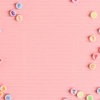 Alfabet kralen grens roze achtergrond