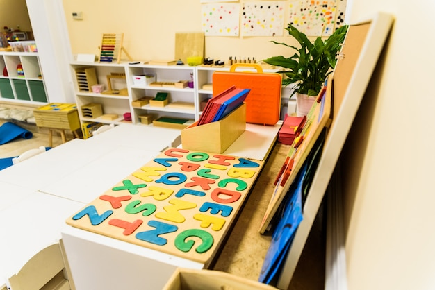 Alfabet met houten letters in een klaslokaal voor kinderen.