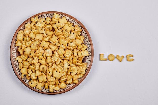 Alfabetcrackers op een keramische plaat en woordliefde gespeld met crackers.