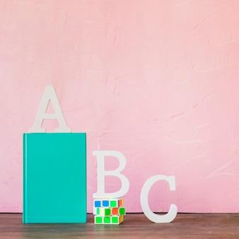 Alfabetletters met boek en rubiks cube op tafel