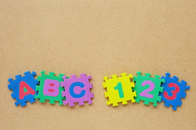 Alfabetpuzzel met nummer puzzel op houten.
