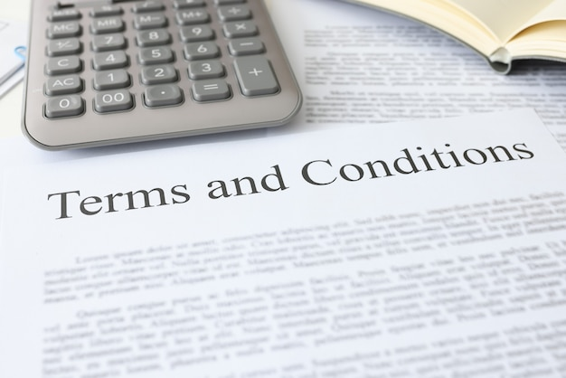 Algemene voorwaarden document met rekenmachine ligt op tafel bankieren commerciële aanbiedingen concept