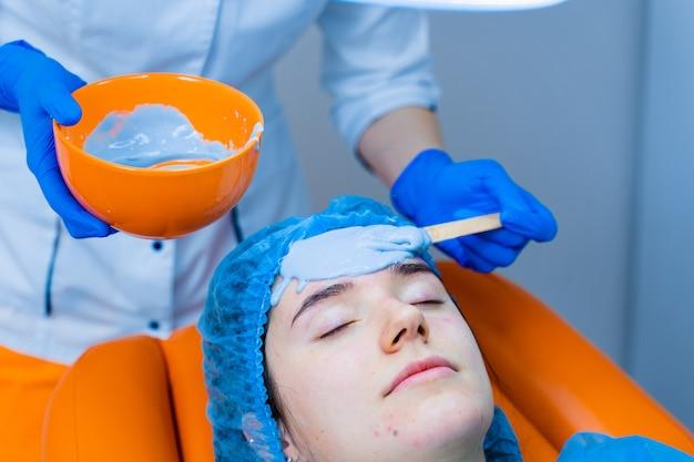 Alginaat hydraterend masker voor gezicht en huid van jonge meisjes. spa-procedure voor verjonging. schoonheidsspecialiste smeert blauw masker uit. dermatologie in de medische kliniek
