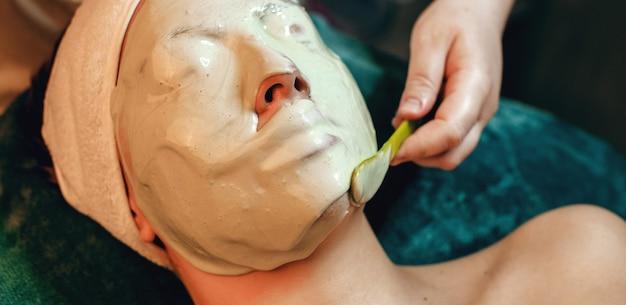 Alginaatmasker aangebracht op het gezicht van een blanke vrouw in de kuuroordsalon terwijl ze ligt
